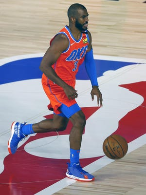 Chris Paul of the Oklahoma City Thunder, wearing Savannah State University-themed sneakers, moves the ball against the Phoenix Suns during a NBA game on Monday night at The Field House in Lake Buena Vista, Florida.