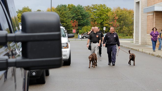 Explosive-sniffing dogs are walked back to their vehicles Wednesday, Oct. 15, 2014, after searching Rushville Middle School. A bomb threat was found in the school and the building was evacuated.