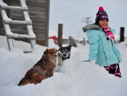 A girl in Browning enjoys the February snowstorm.
