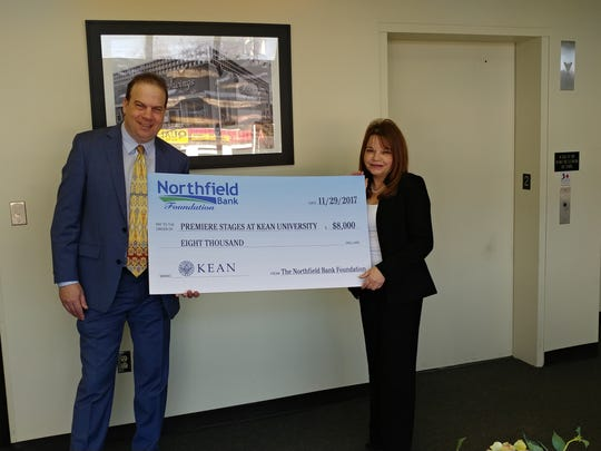 John J. Wooten, Producing Artistic Director of Premiere Stages at Kean University, accepts a donation from Angie Tsirkas, Vice President of Northfield Bank, in support of two playwriting residencies in the Rahway school district.