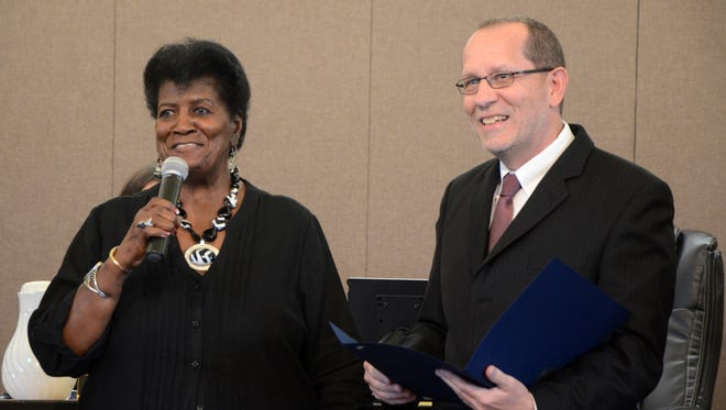"Vivian Laws-Ritter, left, calls her twin sister Velma Laws-Clay ""my very best friend"" before Battle Creek Mayor Dave Walters reads a proclamation recognizing the late community leader's contributions."