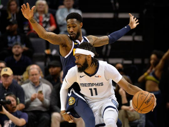 Memphis Grizzlies guard Mike Conley (11) handles the ball against Denver Nuggets guard Will Barton in the first half of an NBA basketball game Monday, Jan. 28, 2019, in Memphis, Tenn. (AP Photo/Brandon Dill)