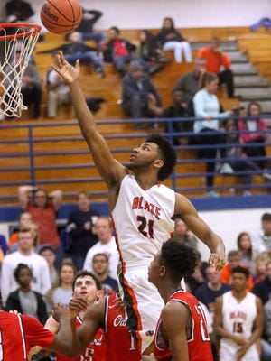 Blackman's Jarrell Reeves (21)  grabs a rebound and goes back for a basket as he is surrounded by Oakland players Cooper Baughn (15), Tre Jones (1) and Travis Jelks (21) during the District 7-AAA boys championship game on Tuesday, Feb. 23, 2016, at La Vergne.