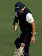 Phil Mickelson clears some sand from his shoes during