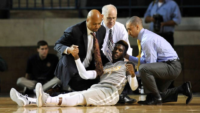 VCU's JeQuan Lewis sits up with the help of head coach Shaka Smart, right, and other team personnel after hitting his head on the floor during the first half  against Tennessee on Friday in Annapolis, Md.