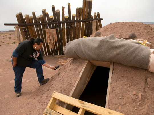 Milton Tso, president of the Cameron Chapter of the Navajo Nation, uses a geiger counter to measure radiation on a sweat lodge adjacent to an abandoned uranium mine in Cameron. Nearby soil potentially from the abandoned mine was used to construct the sweat lodge. Readings on the geiger counter showed twice the level of background readings.