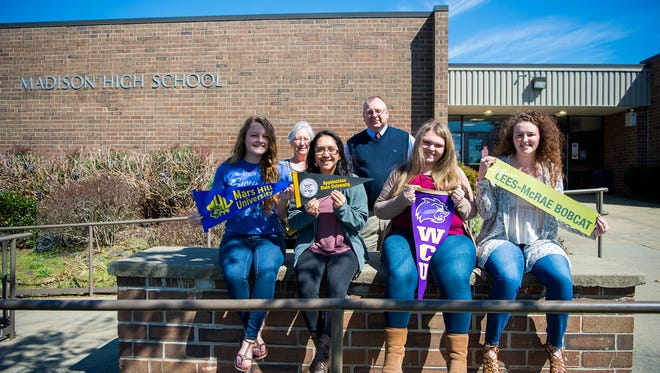 [From left to right back] Nancy Allen and Principal Wesley Floyd stand behind Alexis Wills, Elizabeth Turrubiartes, Katie Wills, and Mikalah Creasman, as they hold up banners for the colleges they plan to attend in front of Madison High School. The four graduating students have been a part of PAGE (Partnership for Appalachian GirlsÕ Education), a literacy program to empower girls through education in Madison County.