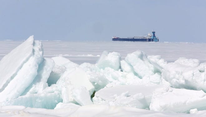 A freighter makes its way along after passing under the Mackinac Bridge on April 15. The shipping season is off to a very slow start because of unseasonably heavy ice.