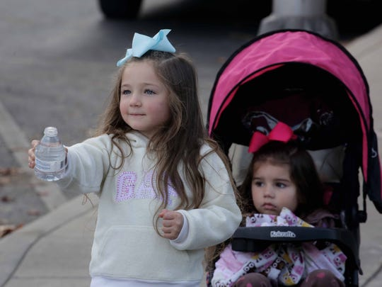 Lillian Shivley, 5, passes out water to runners.
