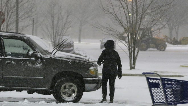 A person brushes snow off a vehicle in the parking lot of Willowbrook Mall, Thursday, Jan. 2, 2014, in Wayne, N.J. Snow and bone-chilling temperatures are expected for the overnight hours with substantial accumulation predicted.