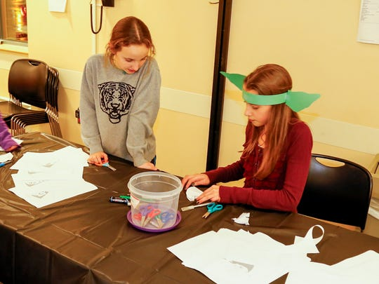 "Geneva Moreland, an eighth-grader, teaches 10-year-old Millie Payton origami at the Tompkins County Public Library's ""Star Wars"" party, an event organized by a teen program at the library."