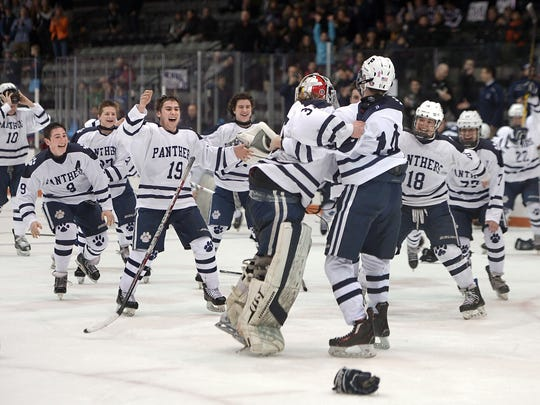 Pittsford players celebrate their win following the Section V Class A hockey championship.