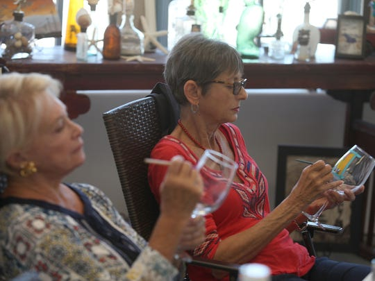 Helen Scheffler, right, and Susan Meyer paint wine glasses during a workshop at Sm'Art Studio art studio in La Quinta, June 15, 2016.