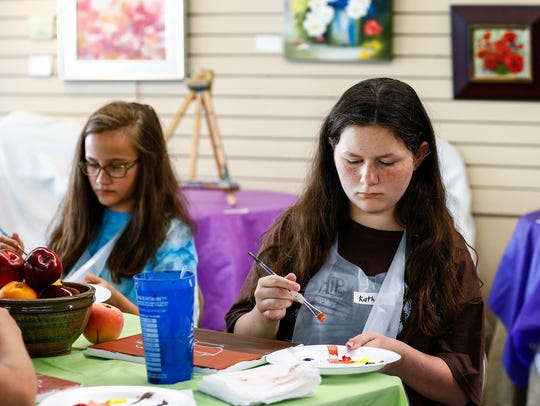 Camper Kathryn Bland, 11, works on a still life painting
