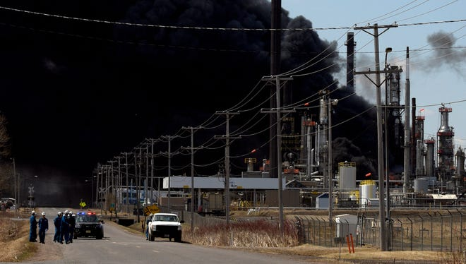 Workers evacuate from an explosion and fire at the Husky Energy oil refinery.