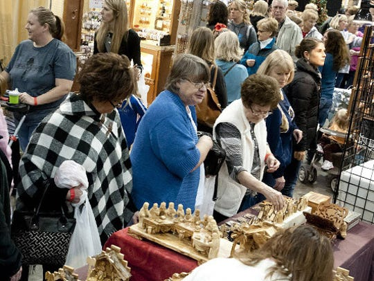 Shoppers peruse a woodworking booth at last year's