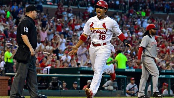 St. Louis Cardinals center fielder Jon Jay (19) celebrates after scoring as Cincinnati Reds starting pitcher Johnny Cueto (47) looks on during the third inning at Busch Stadium.