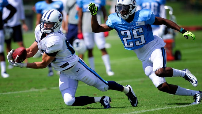 Titans wide receiver Marc Mariani (83) snags a catch in front of cornerback Blidi Wreh-Wilson (25) during practice at St. Thomas Sports Park Monday July 28, 2014, in Nashville, Tenn.