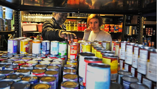 Reilly Gabel helps Jesse Buchanan pick out food from the Little Pantry that Could. At the Little Pantry That Could on Charlotte Avenue, you can pick what foods you take from the shelf. There's no limit to how many weeks you can come for help. The funky, all-volunteer, low-budget pantry takes all comers.