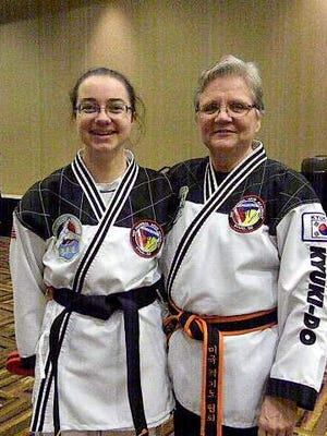 Rebecca Anason poses for a photo with her instructor, Master Linda Imler, after being awarded her new black belt.