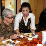 Mary E. Clark is served her Thanksgiving Dinner by 1st New Mexico Bank employee Johana Quintana. The bank has sponsored served the dinner for the past 19 seasons at the Deming Senior Center.