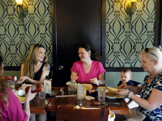 Sisters Nicole Weber of New Cumberland and Jenelle Hood of Wellsville chat while eating lunch at Moonlight Cafe with their mother Carol Eppley of Warrington Township, far left, godmother Kathy Thren of Brooks County and Hood's 9-month-old son Aden in Dover Township.