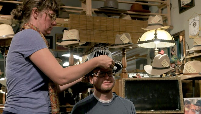 An employee from Optimo Hatworks in Bisbee, Arizona, uses an antique tool to measure reporter Brian Passey's head for a custom hat.