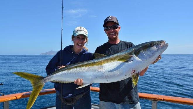 Liz Brannan of Ventura (left) caught a 44.5-pound yellowtail aboard the Erna B.