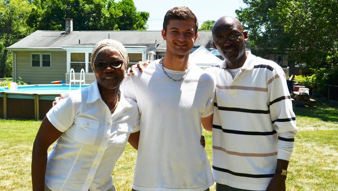 Greg Sampson in the middle, flanked by Patrick Awosogba's parents.