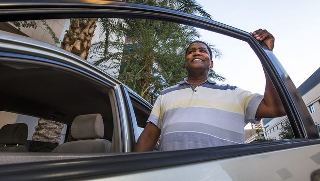 Carl Nicholson of Glendale has been driving for ride-sharing service Uber for the past 10 months. He stands next to his minivan in downtown Phoenix on Nov. 24, 2015.