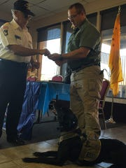Dan Greathouse, president of the Vietnam Veterans of America, Chapter, 961, presents a Purple Heart to Washington County Sheriff's Office Deputy Mike Graf to award his K-9, Tess.
