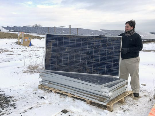 Sean Hutton from a nonprofit solar energy organization shows off a solar panel similar to the ones installed in a solar garden behind him in the Town of Baldwin. The company that built the garden, Delaware River Solar, has three much larger projects planned in Big Flats and Horseheads.
