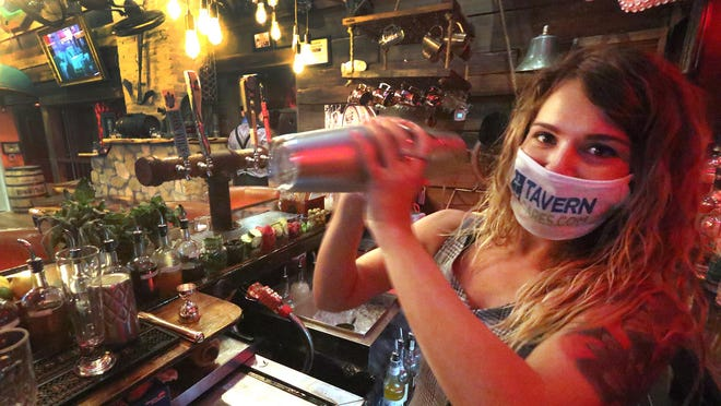 Bartender Kianna Hammersluy makes a drink, Thursday June 4, 2020 for a guest at the Flagler Tavern in New Smyrna Beach.