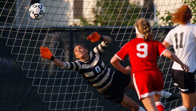 Williamston goalkeeper Grace Kraft dives to deflect a Grosse Ile shot wide as Grosse Ile's Kelsie Krauss (9) and Williamston's Lexi Russell (11) move in Friday, June 10, 2016, at Williamston High School. Williamston fell 0-1.