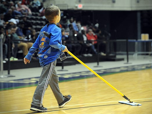 A younger staffer cleans the floor during halftime