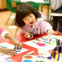 Kindergartner Chloe Chang reacts to discovering that one can use a tissue to apply paint during art class  on Feb. 8 at Pearls Hawthorne School in Yonkers.