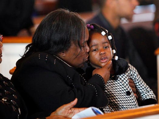Tysean's grandmother, Pearl Williams, left, gives a kiss to Tysean's youngest sister, D'ariana McNish, 4, during funeral services on Nov. 16.