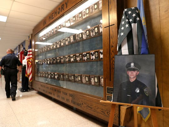 A portrait of Milwaukee Police Officer Charles Irvine Jr. is displayed along with other officers killed in the line of duty over the years. Irvine was killed in June 2018, when the squad in which he was a passenger crashed during the pursuit of a reckless driver.