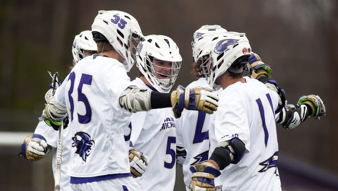 St. Michael's players celebrate a goal during the men's lacrosse game against the Assumption Greyhounds at St. Michael's College on Saturday afternoon.