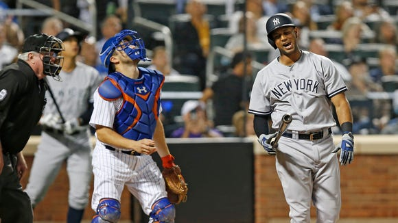 New York Mets catcher Travis d'Arnaud, center, looks up as Yankees Aaron Hicks (31) reacts after flying out in the seventh inning of an interleague baseball game against the New York Mets, Tuesday, Aug. 2, 2016, in New York. Home plate umpire Brian Gorman watches, far left.
