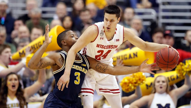 Michigan guard Xavier Simpson (3) reaches for the ball held by Wisconsin guard Bronson Koenig (24) during the first half of U-M's 71-56 win in the Big Ten tournament title game Sunday in Washington.