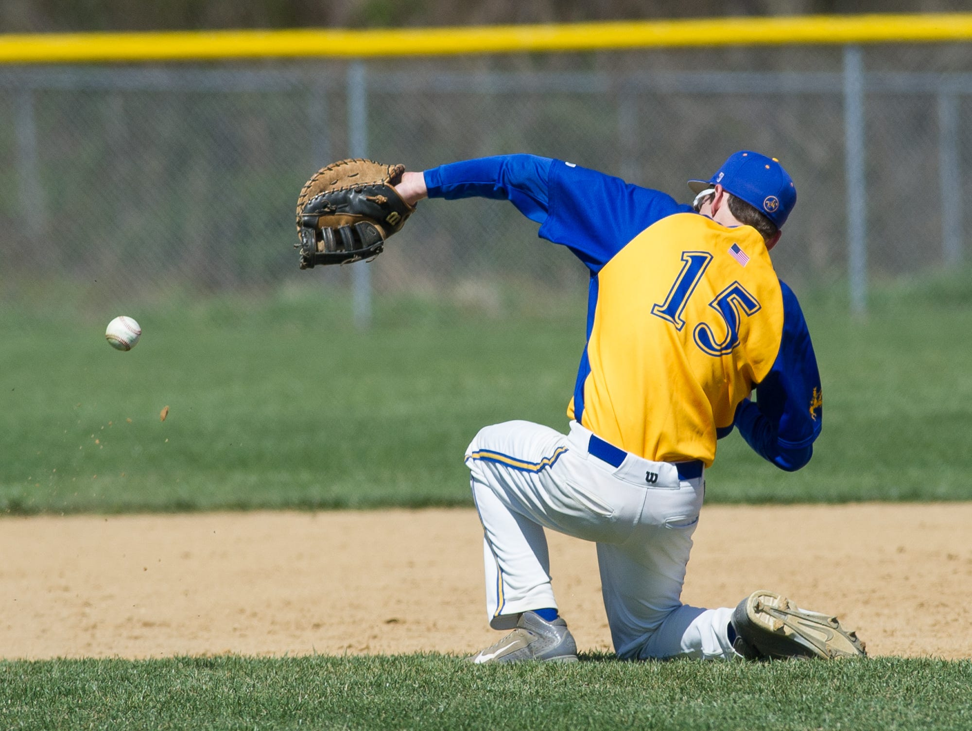 Caesar Rodney's first baseman Robert Williams (15) tries to stop a infield hit in their game against St. Marks.