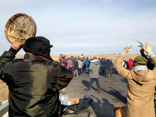 Protesters against the Dakota Access oil pipeline congregate Monday, Nov. 21, 2016, near Cannon Ball, N.D., on a long-closed bridge on a state highway near their camp in southern North Dakota. The bridge was the site of the latest skirmish between protesters and law officers, in which officers used tear gas, rubber bullets and pepper spray, and authorities say protesters assaulted officers with rocks and burning logs.