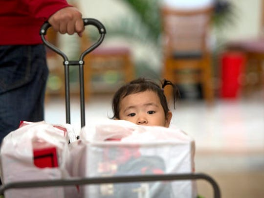 Liang Giang Ying sits in a wagon full of packages as