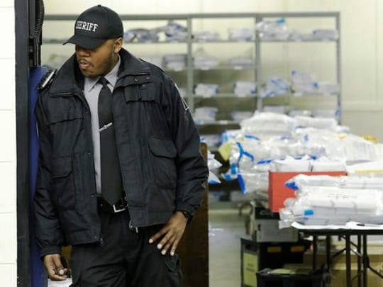 A Milwaukee County sheriff guards a room where ballots are stacked up as a statewide presidential election recount begins Thursday, Dec. 1, 2016, in Milwaukee. The first candidate-driven statewide recount of a presidential election in 16 years began Thursday in Wisconsin, a state that Donald Trump won by less than a percentage point over Hillary Clinton after polls long predicted a Clinton victory.