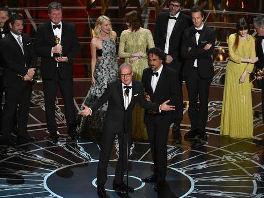 "FILE - This Feb. 22, 2015 file photo shows actor Michael Keaton, foreground center, and director Alejandro G. Inarritu, foreground right, with the cast and crew of ""Birdman or (The Unexpected Virtue of Ignorance)""as they  accept the award for the best picture at the Oscars in Los Angeles."