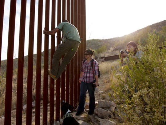 Tim Foley shows how to climb a section of the border wall separating Mexico and the United States as journalists Chitose Nakagawa, right, and Marcie Mieko Kagawa look on in Sasabe, Ariz., in May 2016.