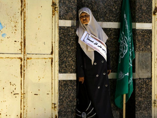 """A woman takes a rests near a green Islamic flag during a rally marking Palestinian prisoners Day in Gaza City, Monday, April 17, 2017. Qadoura Fares, an advocate for prisoners' rights, said Monday, that more than 1,500 Palestinian prisoners have launched an open-ended hunger strike to demand better conditions in Israeli prisons, including more contact with relatives, and an end to Israel's practice of detentions without trial. Arabic reads, """" freeing prisoners is a duty of every Muslim""""."""