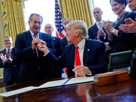 FILE - In this Feb. 24, 2017, file photo, President Donald Trump gives the pen he used to sign an executive order to Dow Chemical President, Chairman and CEO Andrew Liveris, as other business leaders applaud in the Oval Office of the White House in Washington. Dow Chemical is pushing the Trump administration to scrap the findings of federal scientists who point to a family of widely used pesticides as harmful to about 1,800 critically threatened or endangered species. Liveris is a close adviser to President Donald Trump. The company gave $1 million for Trump's inaugural activities.