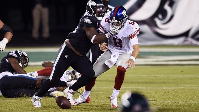 New York Giants' Daniel Jones fumbles after being hit by Philadelphia's 'Brandon Graham on Thursday night in Philadelphia.